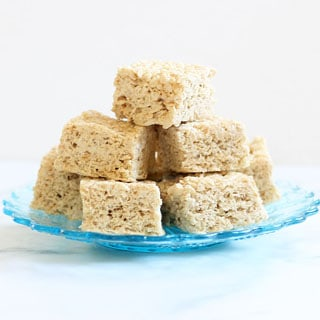 brown butter rice krispie treats stacked up on a blue glass plate