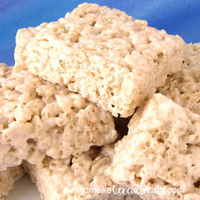 the very best rice krispie treats are piled up on a white platter set in front of a blue background