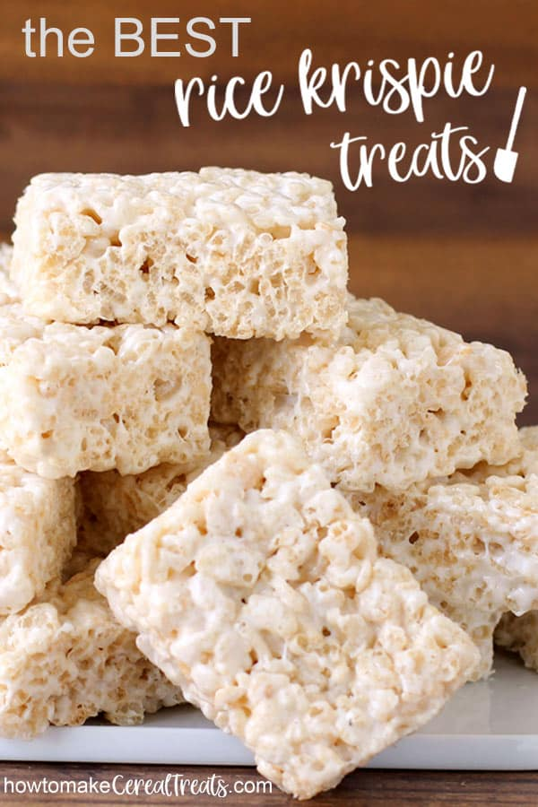 rice krispie treats stacked up in a pile on a white black in front of a wood backdrop