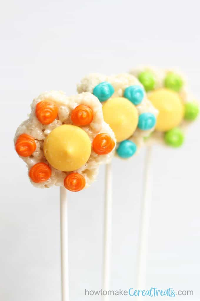 flower rice krispie treats on sticks with white background