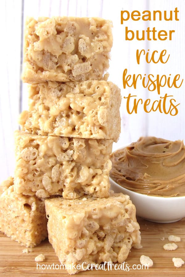 a stack of peanut butter rice krispie treats set on a wood cutting board set next to a small white bowl filled with creamy peanut butter all set in front of a wood slat background