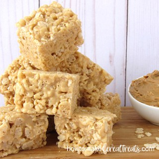 gooey peanut butter rice krispie treats stacked on top of each other on a wooden cutting board set next to a bowl of creamy peanut butter