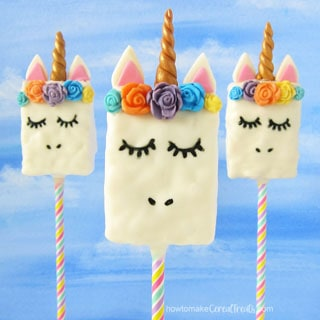 Rice Crispy Treat Unicorns on rainbow paper straws on a blue background