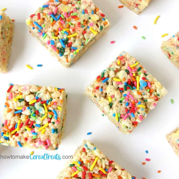 rice krispie treats topped with lots of rainbow sprinkles are scattered around a white countertop