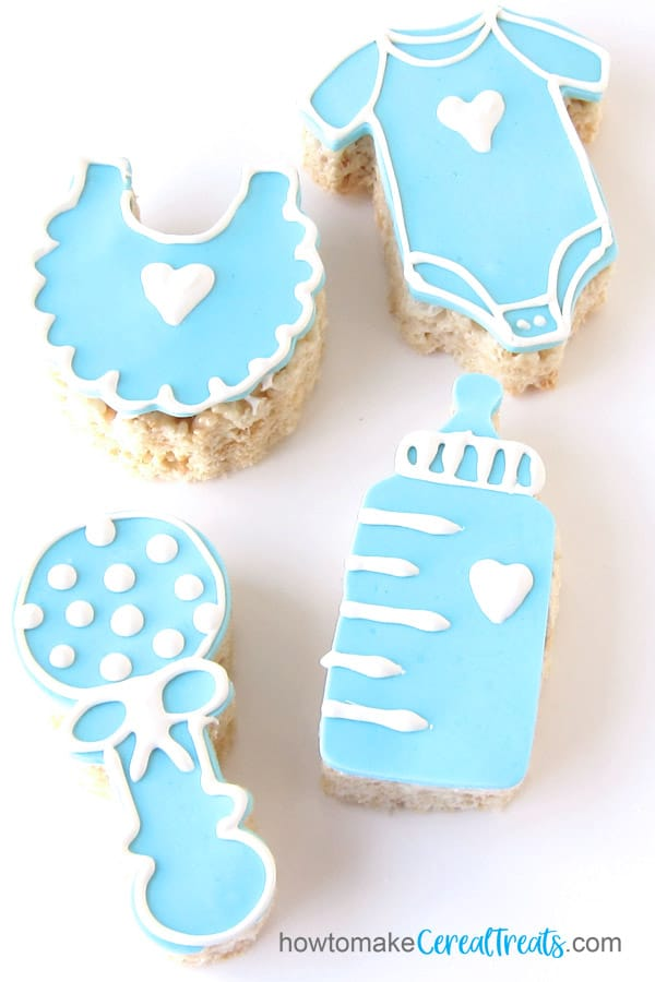 baby shower rice krispie treats including modeling chocolate decorated bib, onesie, rattle, and baby bottle
