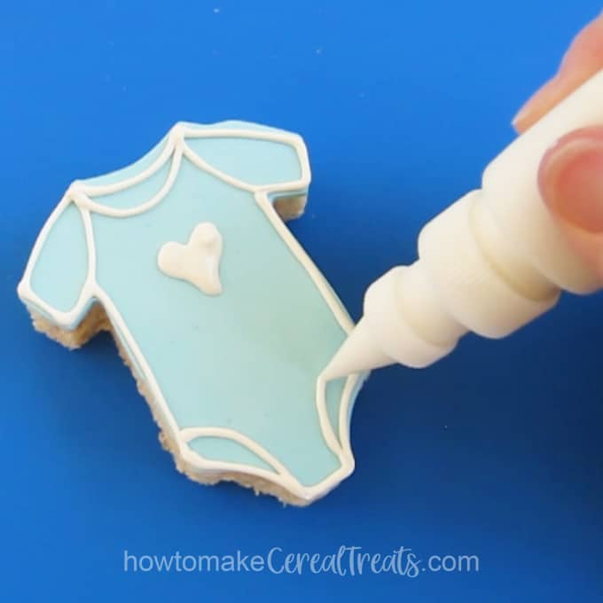piping decorations onto a baby shower rice crispy treat