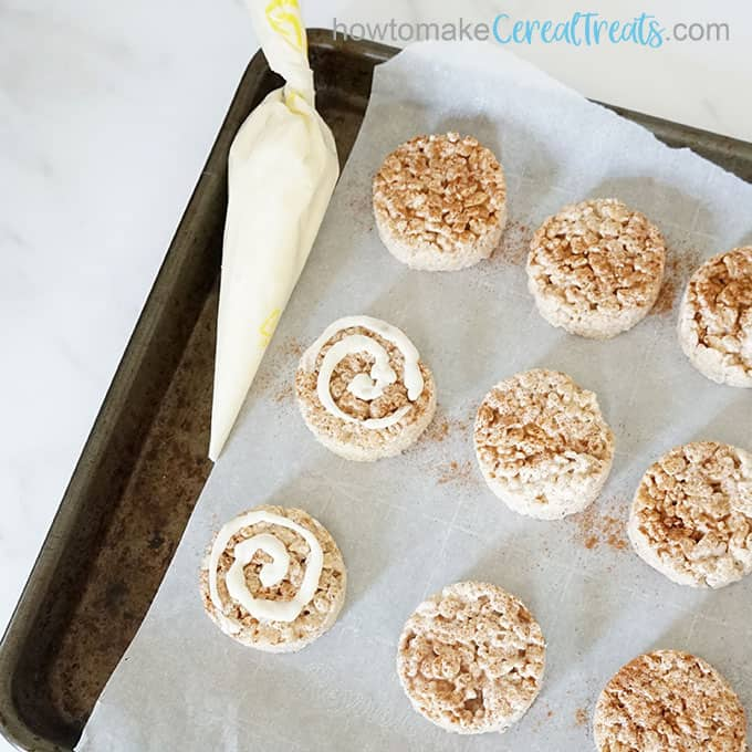 frosting cinnamon roll rice krispie treats on baking tray