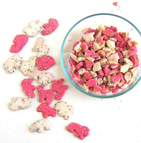 Circus Animal Cookies coated in pink and white frosting and rainbow sprinkles.