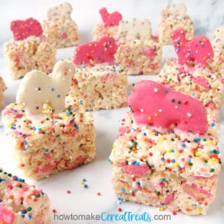 Pink and white Circus Animal Cookies top rice crispy treats loaded with more cookies and rainbow sprinkles.