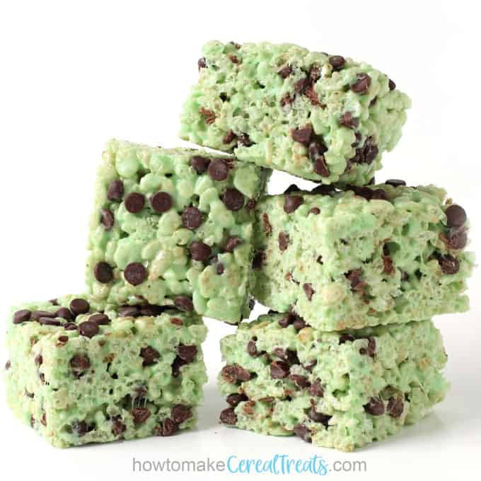 Square mint chocolate chip rice crispy treats stacked on top of each other