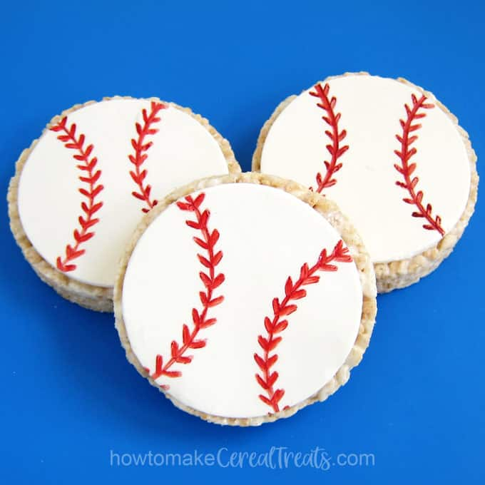 3 rice crispy treat baseballs on a blue silicone mat