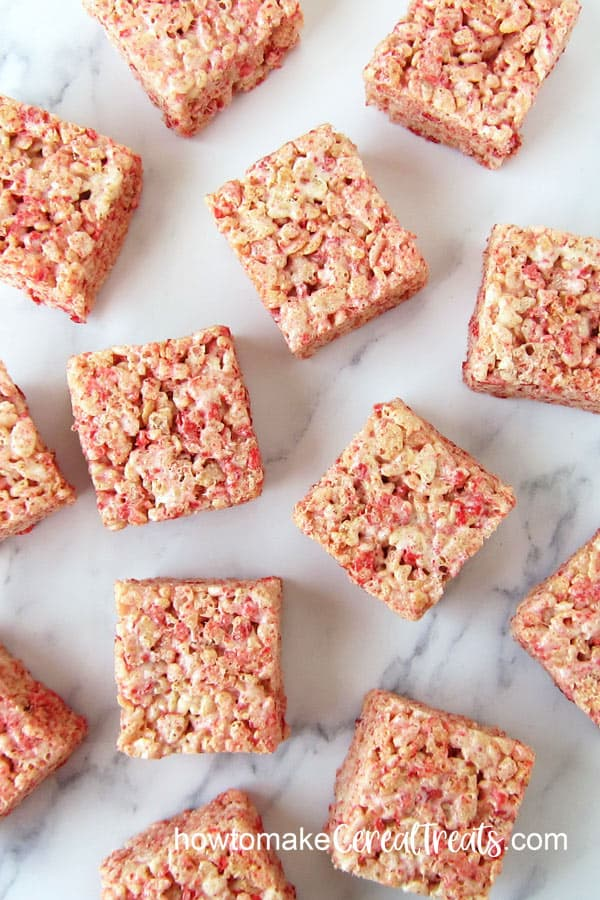 square strawberry rice krispie treats on a marble countertop