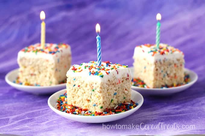sprinkle topped birthday cake rice krispie treats with birthday candles on a purple background