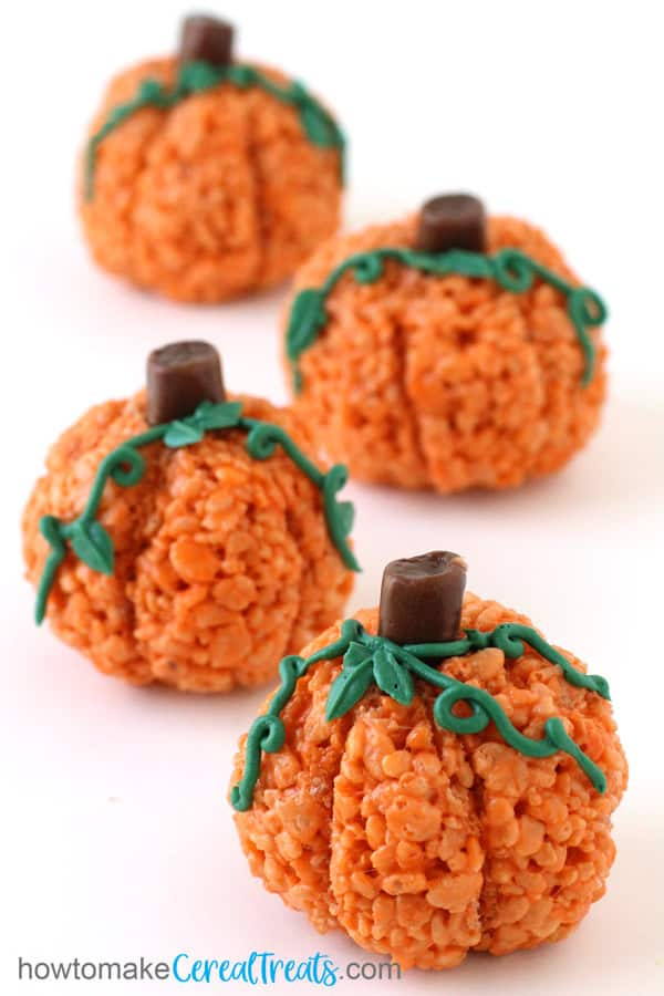 Halloween rice Krispie Treat pumpkins with green frosting vines and leaves