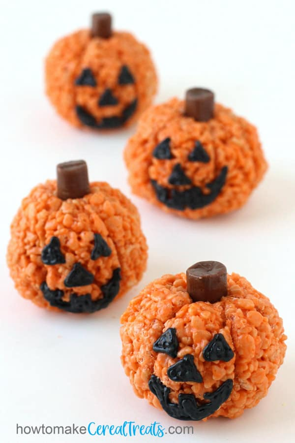 Rice Krispie Treat Jack-O-Lanterns are decorated with black frosting faces and Tootsie Roll stems