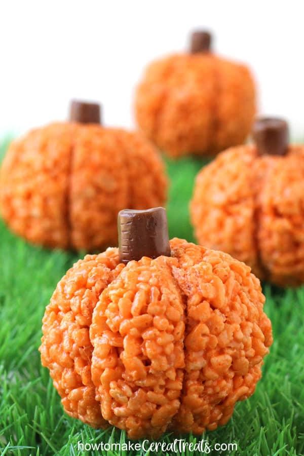 Rice Krispie Treat Pumpkins with Tootsie Roll stems sitting on green plastic grass