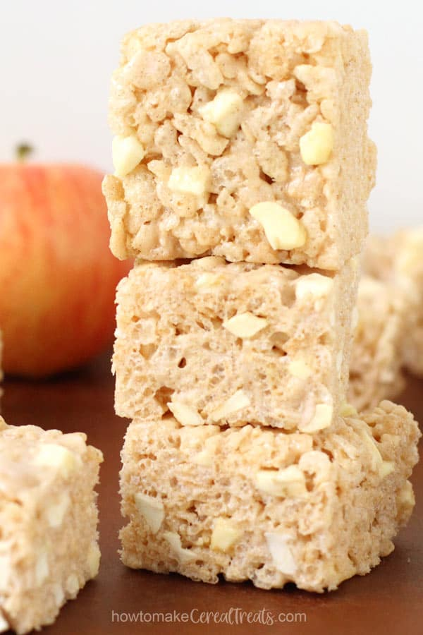 Apple Cinnamon Rice Krispie Treats stacked up in front of an apple.