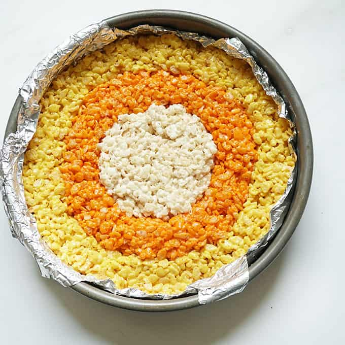 preparing candy corn Rice Krispie treats in baking pan