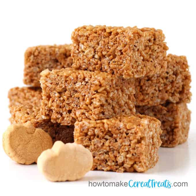pumpkin marshmallow cereal treat squares stacked behind pumpkin spice marshmallows