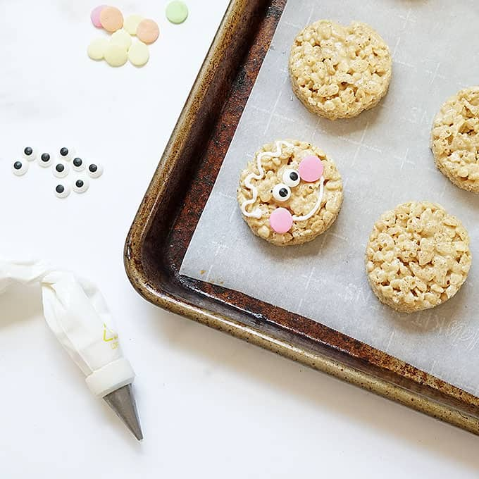 decorating gingerbread Rice Krispie treats with royal icing to look like gingerbread man cookies