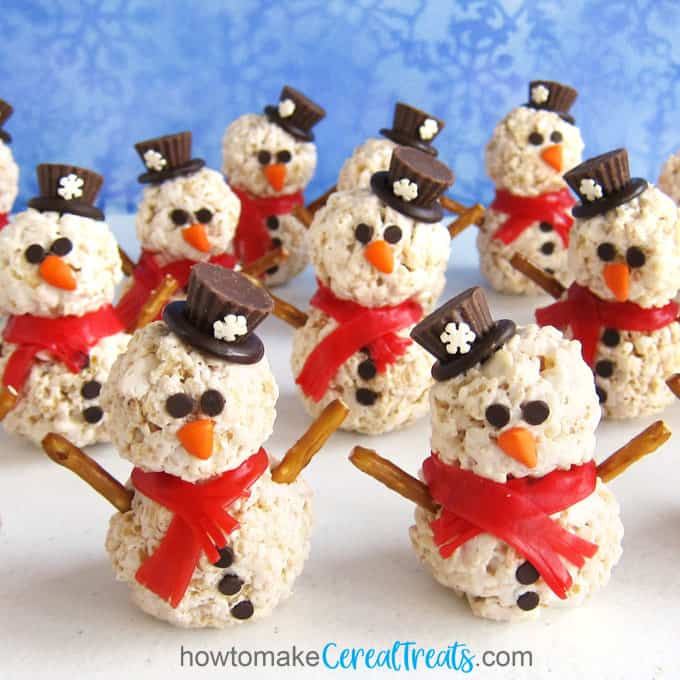 rice crispy treat snowmen arranged on a white table set in front of a snowflake background