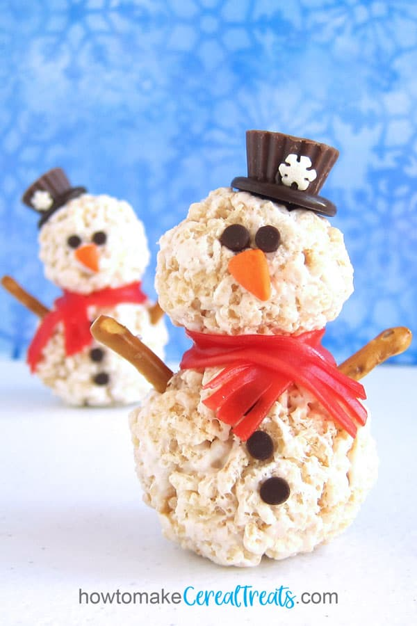 rice krispie treat snowmen with mini Reese's cup hats, fruit roll scarves, chocolate chip eyes, Starburst carrot nose, and pretzel stick arms.