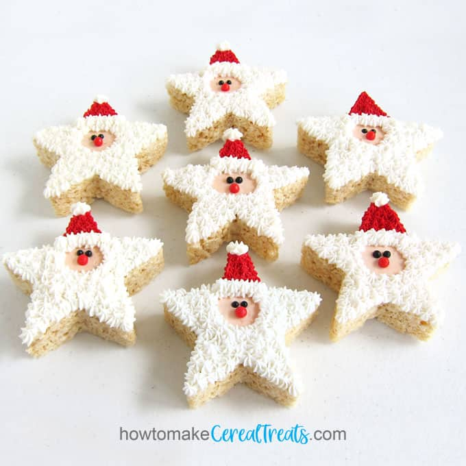 7 Santa Rice Krispie Treats with red hats and white beards arranged on a white table